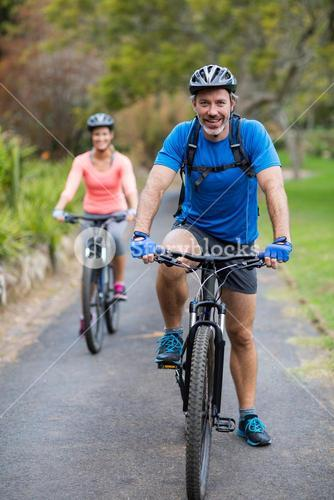 Athletic couple cycling on the road