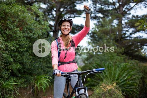 Athletic woman standing with mountain bike