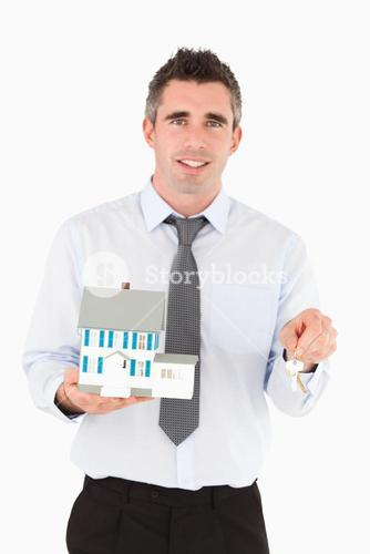 Man holding a key and a miniature house