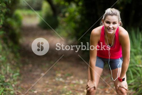 Tired woman taking a break while jogging