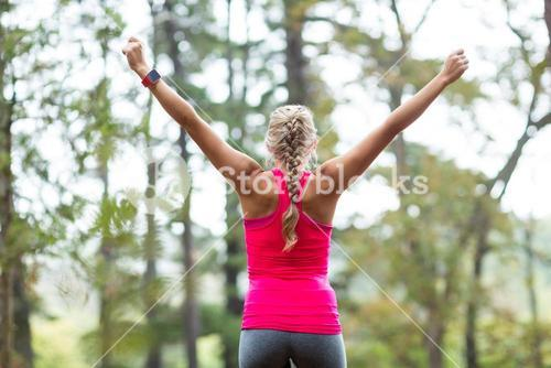 Excited woman standing in forest