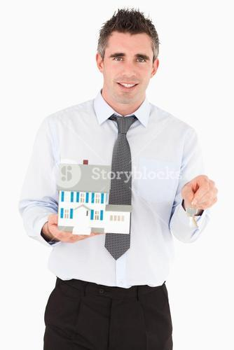 Businessman holding a key and a miniature house