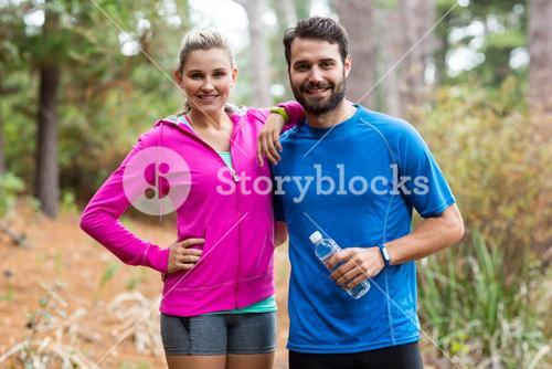 Athletic couple standing together in forest