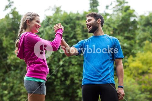 Athletic couple holding hands in forest