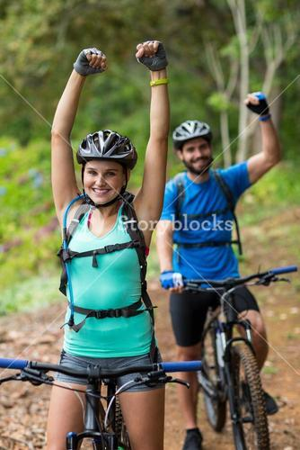 Athletic couple standing with mountain bike in forest