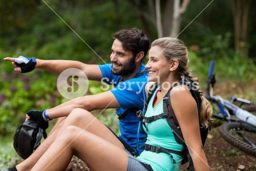 Athletic couple pointing at nature