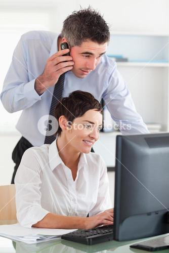 Man making a phone while looking at his colleagues screen