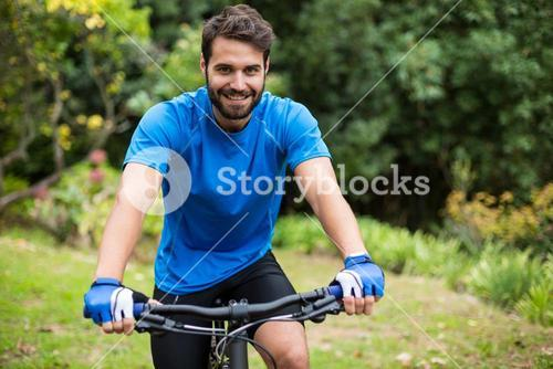 Male athletic standing with mountain bike in forest