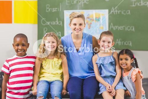Portrait of teacher and kids in classroom