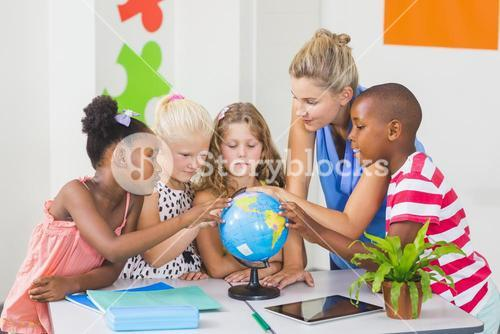 Teacher discussing globe with kids