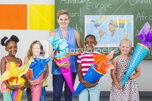 Happy kids and teacher holding gifts in classroom