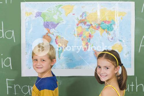 School kids pointing at map in classroom