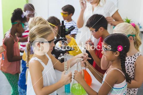Kids doing a chemical experiment in laboratory
