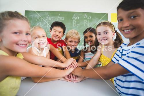 School kids stacking hands in classroom