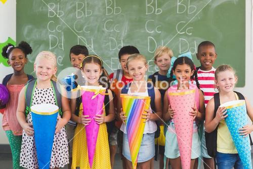 Happy kids holding gifts in classroom