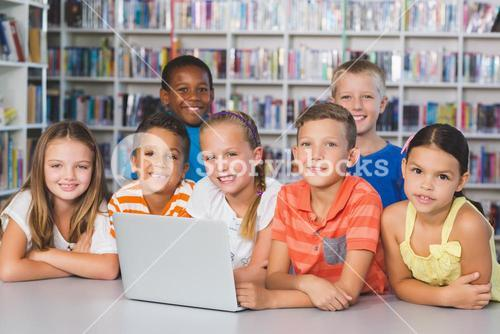Portrait of school kids using laptop in library