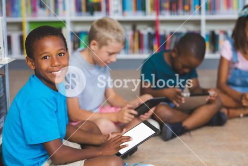 School kids sitting on floor using digital tablet in library