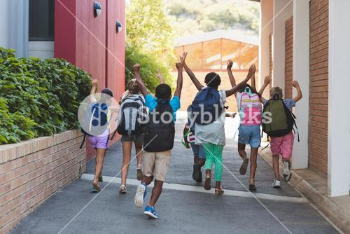 Rear view of classmates running at school campus