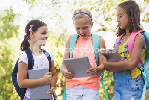 Happy school kids using digital tablet