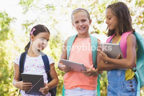 Portrait of school kids using digital tablet