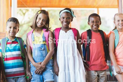 Group of smiling school kids standing in row
