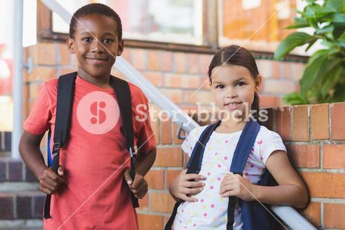 Smiling school kids standing on staircase