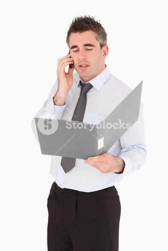 Portrait of a businessman making a phone call while holding a binder