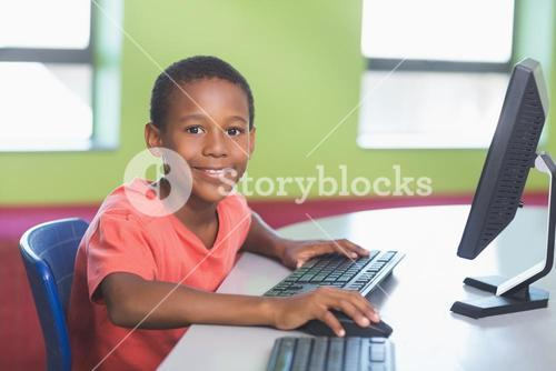 Schoolboy using computer in classroom