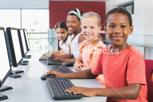 School kids using computer in classroom
