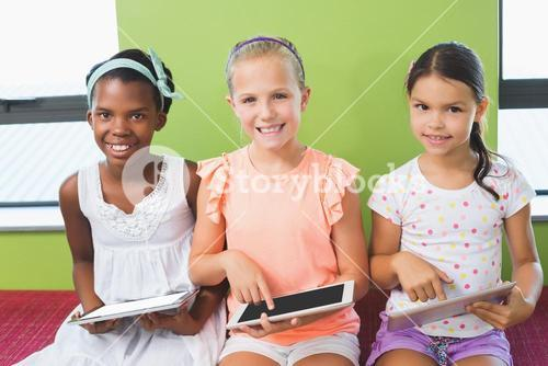 Schoolgirls using digital tablet in library