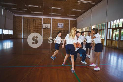Sports teacher and school kids playing basketball