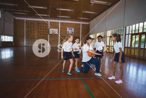 Sports teacher teaching school kids to play basketball