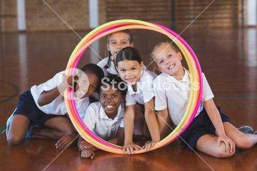 School kids looking through hula hoop in basketball court