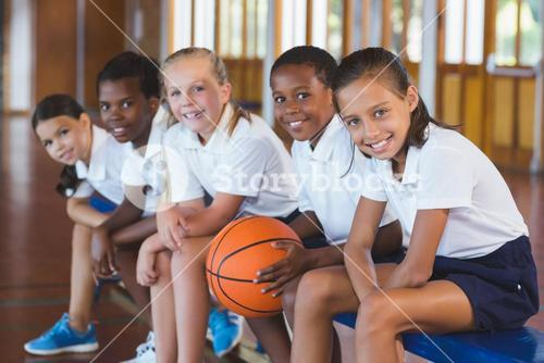 Portrait of school kids sitting in basketball court