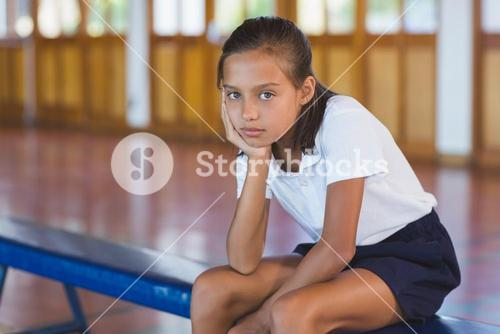 Portrait of schoolgirl sitting in basketball court