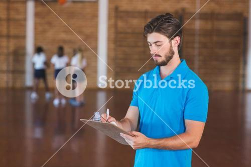 Sports teacher writing on clipboard