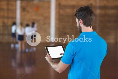 Sports teacher using digital tablet