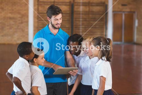 Sports teacher and school kids using digital tablet in basketball court