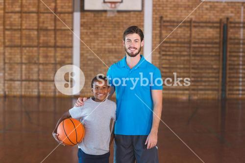 Portrait of sports teacher standing with his student in basketball court