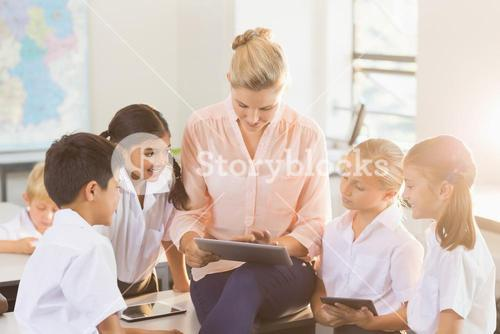 Teacher teaching kids on digital tablet