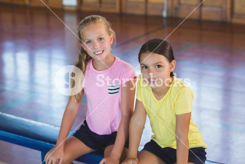 Girls sitting on bench in basketball court