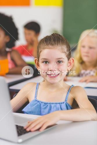 Schoolgirl using laptop in classroom