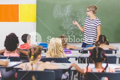 Teacher teaching mathematics to school kids in classroom