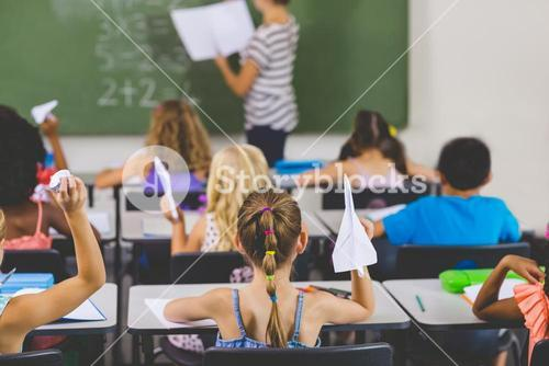 school kids with paper planes in classroom