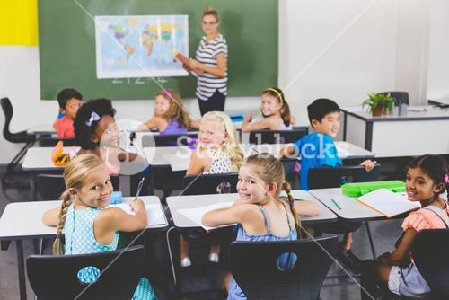 School kids smiling during geography class