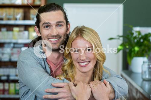Portrait of happy couple embracing each other in a coffee shop