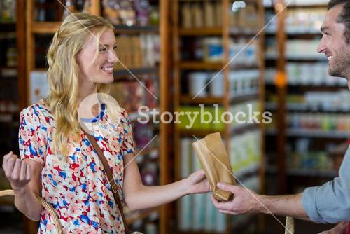 Smiling woman purchasing groceries