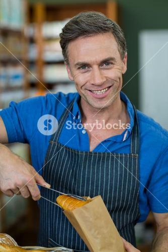 Portrait of smiling male staff packing bread in paper bag