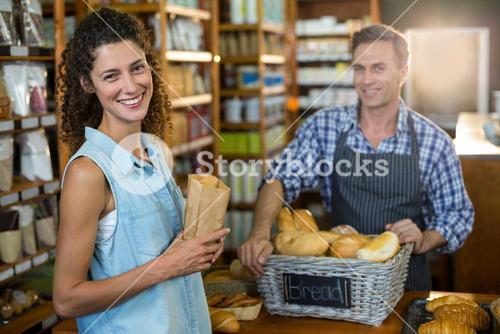 Portrait of smiling woman purchasing bread at bakery store
