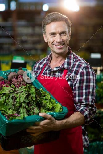 Smiling male staff holding a crate of fresh vegetables at supermarket